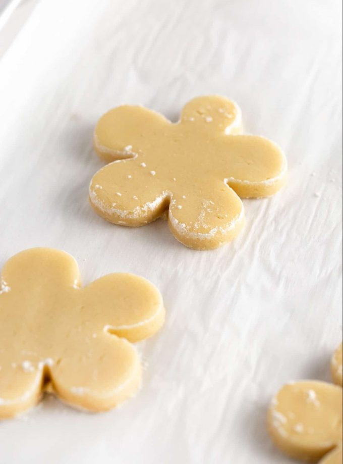 Flower shaped sugar cookie dough on baking sheet