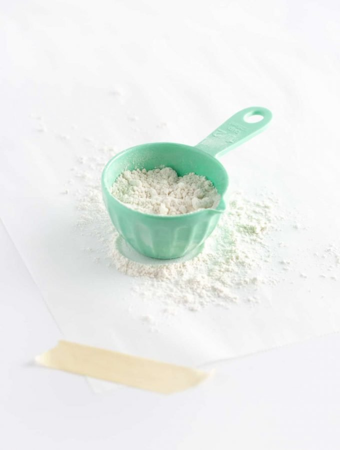 Blue measuring cup of flour on parchment paper
