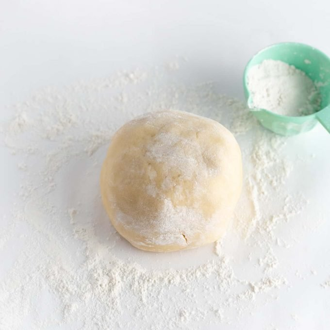 ball of raw sugar cookie dough with flour on top