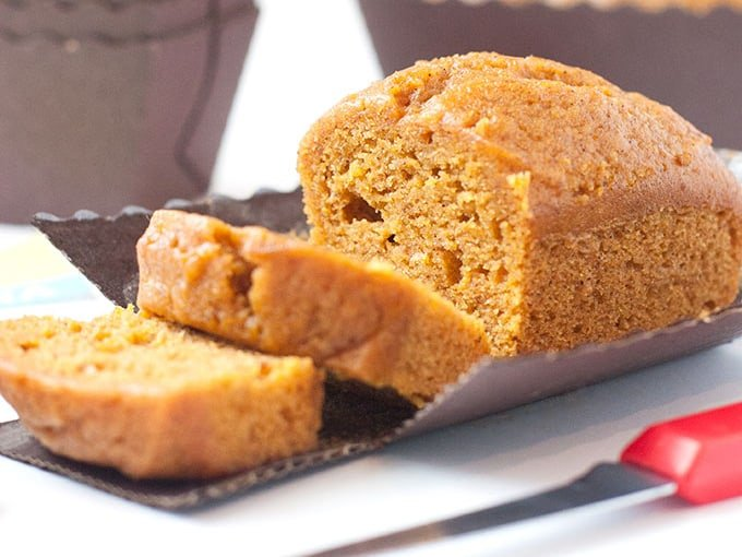 Moist pumpkin bread mini loaf pan recipe in tiny disposable loaf pans cut in slices with red knife.