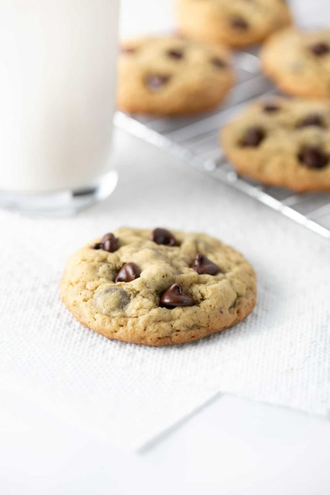 Warm chewy chocolate chip oatmeal cookie with glass of milk