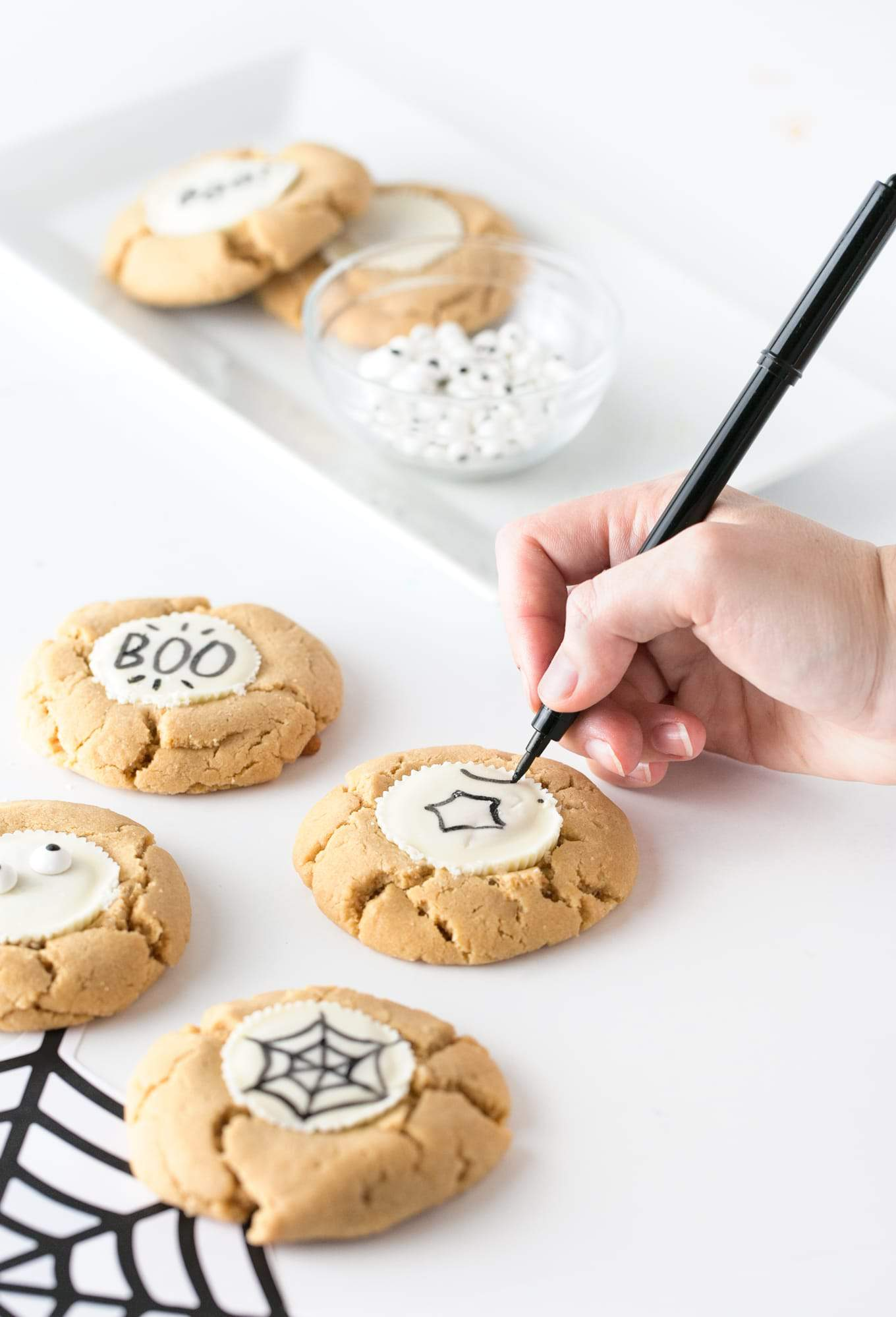 """Forget the fancy decorating and grab the edible food pen to draw-your-own easy Halloween cookies! Using a traditional peanut butter cup as the """"canvas"""", you can customize with your own icons, faces or spooktacular phrases! #Halloween 