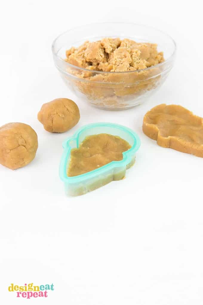 Pressing peanut butter cookie dough into plastic Sugarbelle ice cream cone cutter.