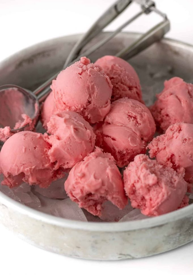 Scoops of raspberry sherbet on ice in metal baking pan