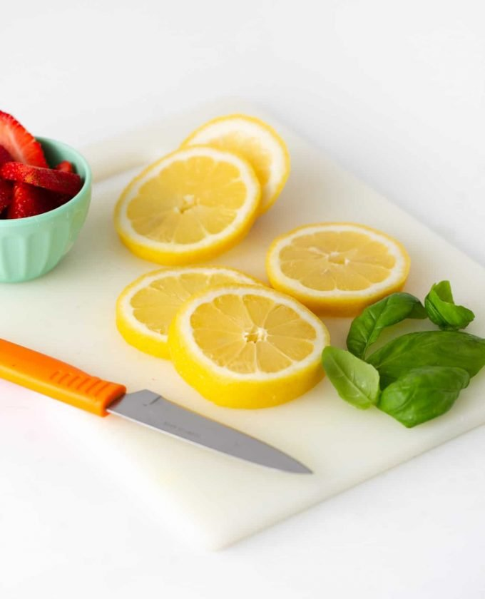 Lemon slices on cutting board with strawberries and basil