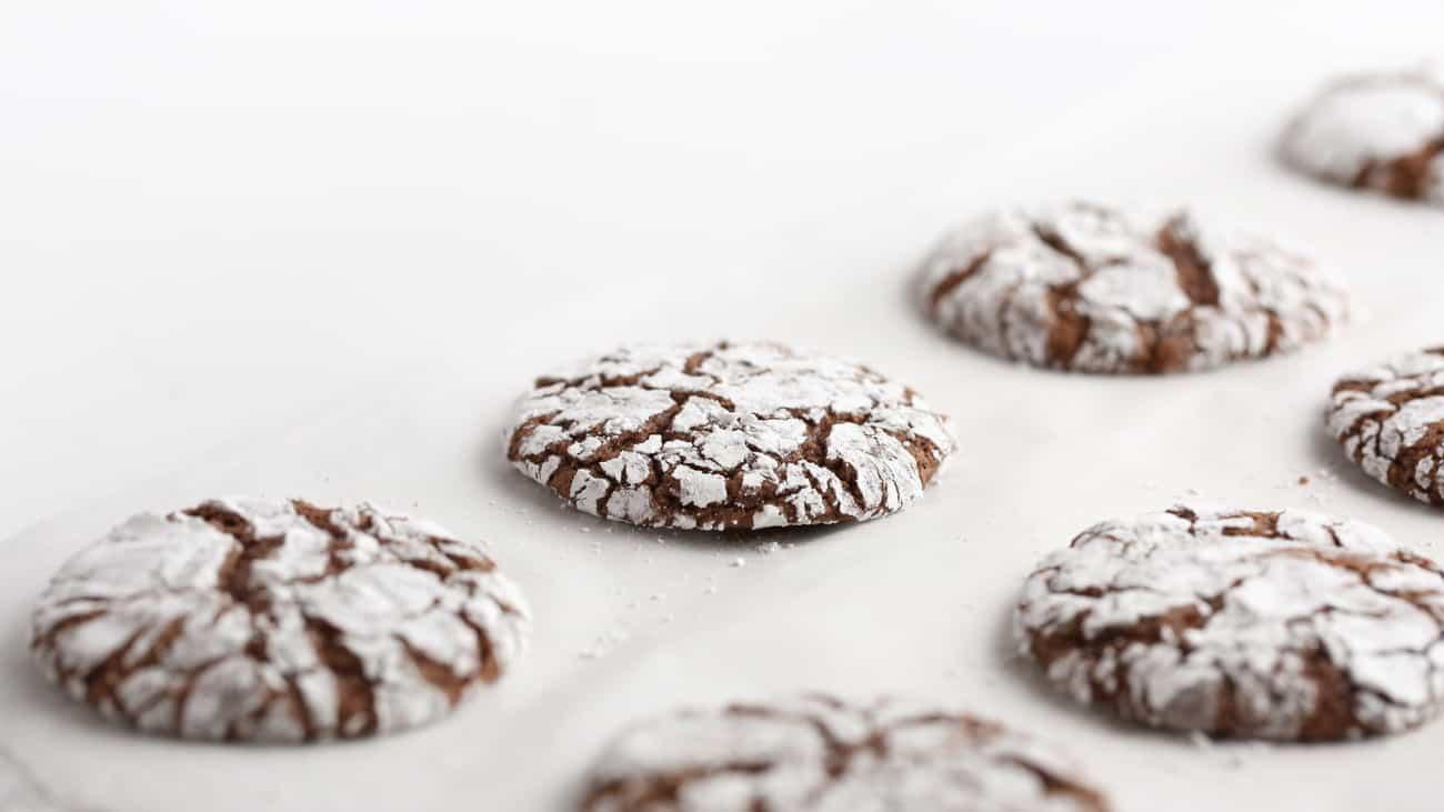 Baking sheet of baked crackle top chocolate brownie cookies.