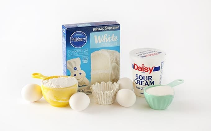 ingredients for white cake mix, includes pillsbury white boxed cake mix, sour cream, eggs, sugar, flour, and cupcake liner