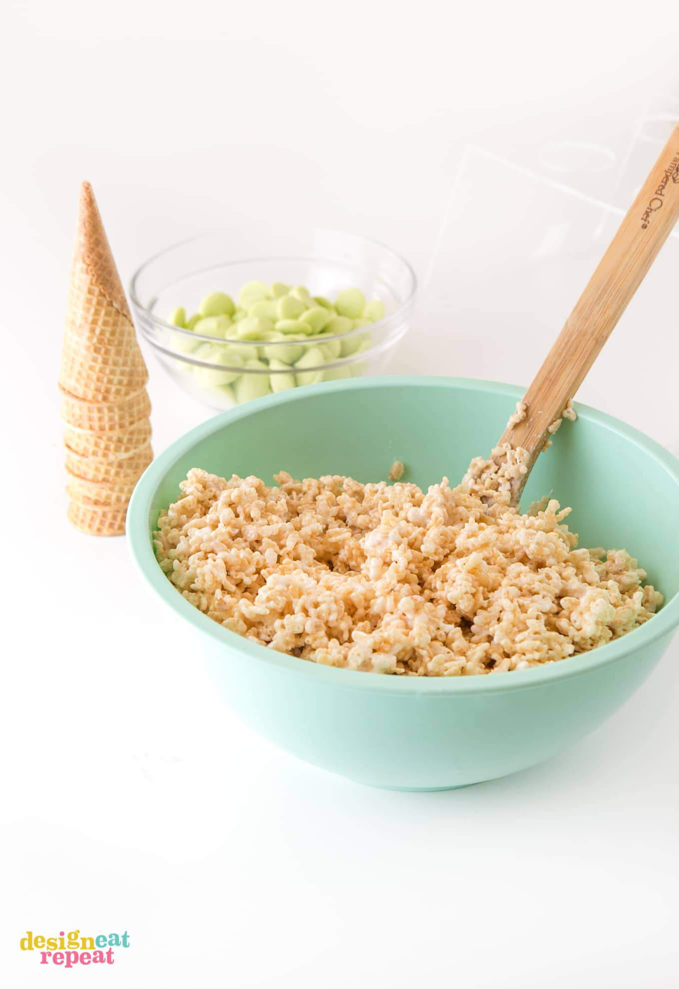 mixing rice krispy cereal treats with wooden spoon in large blue bowl